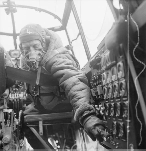 The Flight Engineer adjusts an instrument on board a Lancaster.